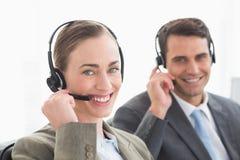 Бизнесмены с шлемофонами усмехаясь на камере Стоковое Изображение