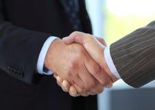 Бизнесмены трястия руки над делом Стоковое Фото