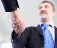 Бизнесмены трястия руки над делом Стоковая Фотография