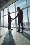 Бизнесмены трясут руки друг с другом стоя против панорамных окон Стоковая Фотография