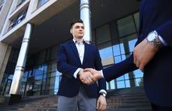 Бизнесмены тряся руки вне современного офисного здания Стоковые Изображения RF