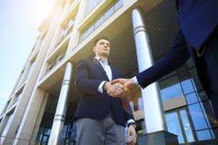 Бизнесмены тряся руки вне современного офисного здания Стоковая Фотография RF