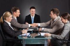 Бизнесмены тряся руки во время встречи конференции Стоковая Фотография