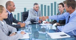 Бизнесмены тряся руки во время встречи против диаграммы в предпосылке Стоковое Изображение