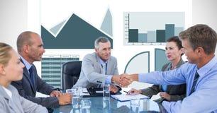 Бизнесмены тряся руки во время встречи с диаграммами в предпосылке Стоковое Изображение