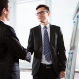 Бизнесмены тряся руки в офисе Стоковое фото RF