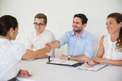 Бизнесмены тряся руки в офисе Стоковое Фото