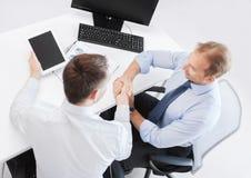Бизнесмены тряся руки в офисе Стоковые Изображения