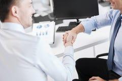 Бизнесмены тряся руки в офисе Стоковое Изображение