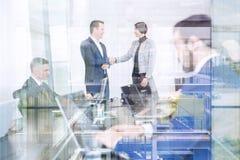 Бизнесмены тряся руки в офисе moder корпоративном Стоковые Фотографии RF