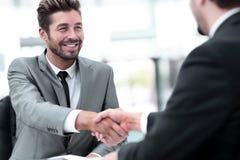 2 бизнесмены тряся руки и смотря один другого с Стоковые Фотографии RF