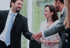 2 бизнесмены тряся руки и смотря один другого с Стоковая Фотография RF