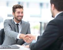 2 бизнесмены тряся руки и смотря один другого с Стоковая Фотография