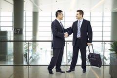 Бизнесмены тряся руки на авиапорте Стоковое Изображение RF