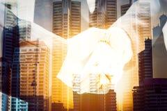 Бизнесмены тряся руки, на предпосылке конструкции и строить, концепция успеха в бизнесе Стоковое фото RF