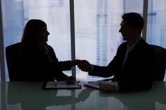 Бизнесмены тряся руки на столе офиса Стоковое Изображение