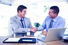 Бизнесмены тряся руки на столе Стоковые Изображения RF