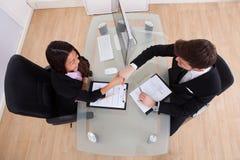 Бизнесмены тряся руки на столе Стоковая Фотография