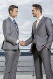 Бизнесмены тряся руки на террасе против неба Стоковая Фотография RF