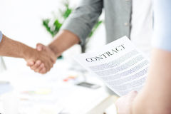 Бизнесмены тряся руки пока коллега держа контракт Стоковая Фотография