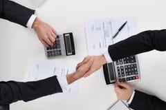 Бизнесмены тряся руки пока расчетливый финансируют на столе Стоковое фото RF