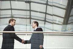 Бизнесмены тряся руки против стеклянных перил Стоковая Фотография RF