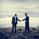 Бизнесмены тряся руки с бурной предпосылкой океана Стоковое Изображение RF