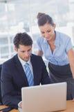 Бизнесмены усмехаясь и работая вместе с компьтер-книжкой Стоковые Фотографии RF