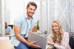 Бизнесмены усмехаясь и работая вместе с компьтер-книжкой Стоковые Изображения