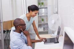 Бизнесмены усмехаясь и работая вместе с компьтер-книжкой Стоковое Изображение RF