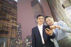 2 бизнесмены усмехаясь и смотря телефон Стоковое фото RF
