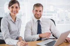 Бизнесмены усмехаясь на камере с компьтер-книжкой Стоковая Фотография RF