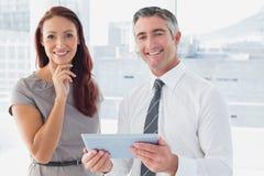Бизнесмены усмехаясь на камере Стоковая Фотография