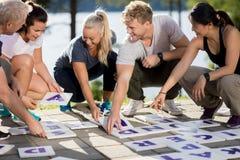 Бизнесмены усмехаясь пока разрешающ кроссворд на патио стоковое изображение