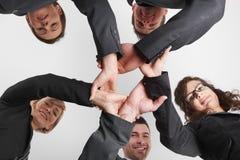Бизнесмены формируя кольцо угла рук низкого стоковое изображение