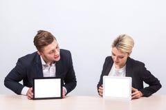 Бизнесмены человека и женщины сидя на таблице и взгляде int Стоковое Изображение