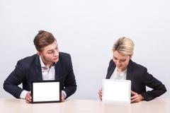Бизнесмены человека и женщины сидя на таблице и взгляде int Стоковые Фото