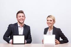 Бизнесмены человека и женщины сидя на таблице и смотря a Стоковое Изображение
