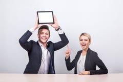 Бизнесмены человека и женщины сидя на таблице, человек держат Стоковые Изображения RF