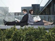 Бизнесмены читая газеты на стене Стоковые Фото