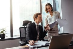 Бизнесмены читая документы в офисе стоковое изображение