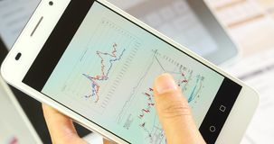бизнесмены 4k просматривая долевые диограммы финансов & тенденцию запаса на smartPhone акции видеоматериалы