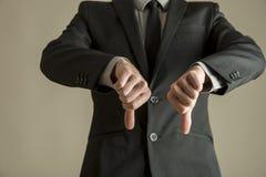 Бизнесмен давая большие пальцы руки вниз подписывает Стоковые Изображения RF