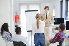 Бизнесмен давая представление к его коллегам на работе стоя перед flipchart Стоковые Изображения