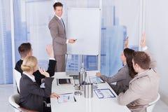 Бизнесмен давая представление к коллегам на офисе Стоковое Фото