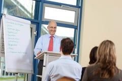 Бизнесмен давая представление к сотрудникам пока стоящ на p Стоковое Изображение