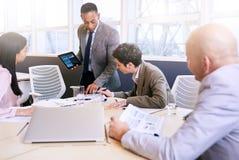 Бизнесмен давая представление с электронной таблеткой в его руках Стоковое Изображение RF