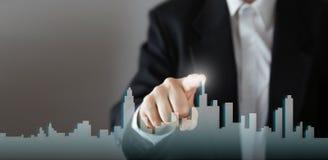 Бизнесмен активирует процесс роста, выбирая дом, концепция города недвижимости Отжимать руки горизонта значок дома дальше Стоковая Фотография RF