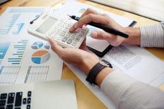 Бизнесмен анализируя диаграммы вклада и отжимая калькулятор Стоковая Фотография
