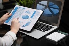 Бизнесмен анализируя диаграммы вклада с компьтер-книжкой Бухгалтерский учет стоковые изображения